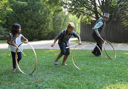 youngsters practice rolling hoops at Black Creek Pioneer Village on Guide and Scout Day