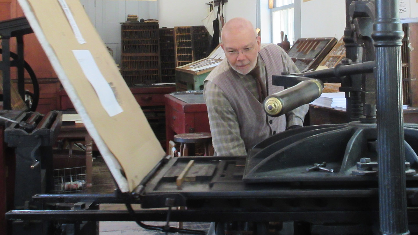 a volunteer works in the Black Creek Pioneer Village Printing Office