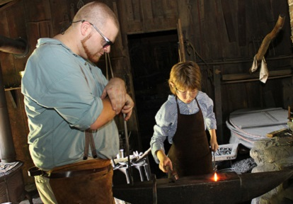 a blacksmith and apprentice work together at Black Creek Pioneer Village