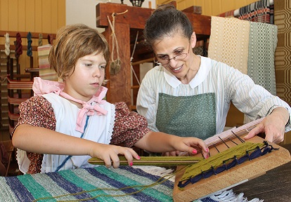 young girl and older woman in pioneer costume do textile work