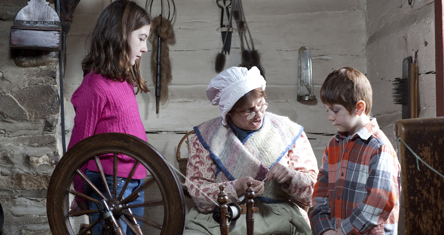 Black Creek Pioneer Village interpreter demonstrates a spinning wheel for elementary school students