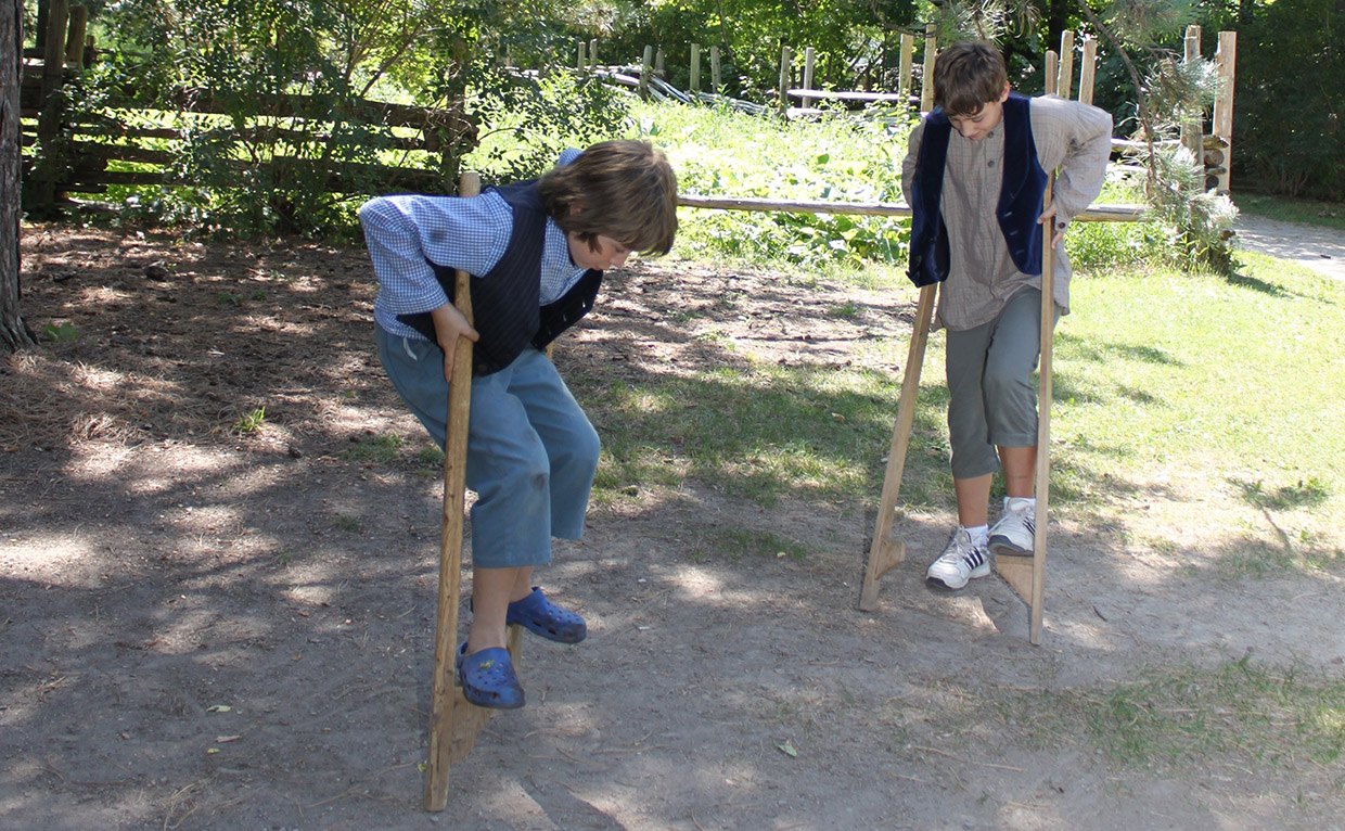 youngsters practice walking on stilts at Black Creek Pioneer Village