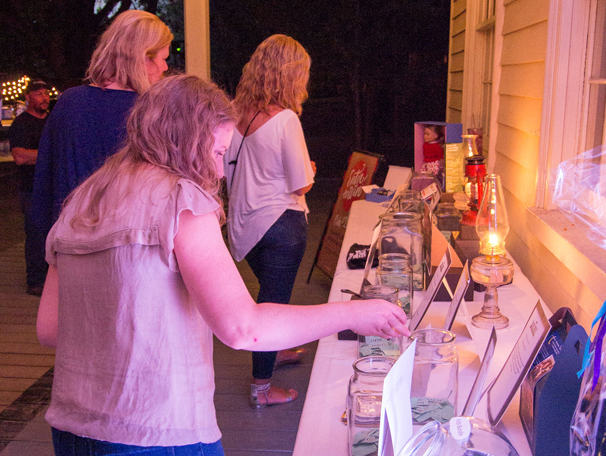Visitors to Black Creek Pioneer Village take part in a silent auction during the Light Up the Night event