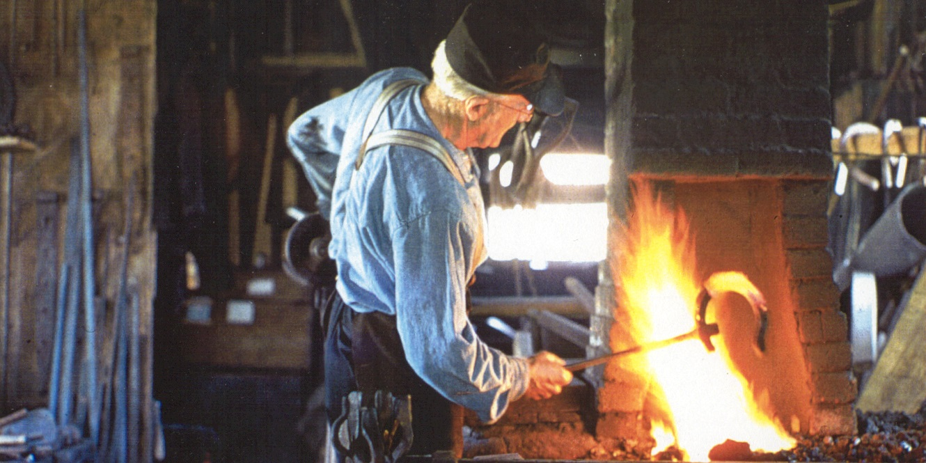 a volunteer works in the Black Creek Pioneer Village blacksmith shop