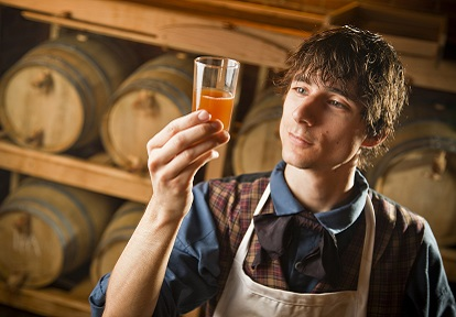 Black Creek Brewery interpreter holds a small glass of beer up to the light