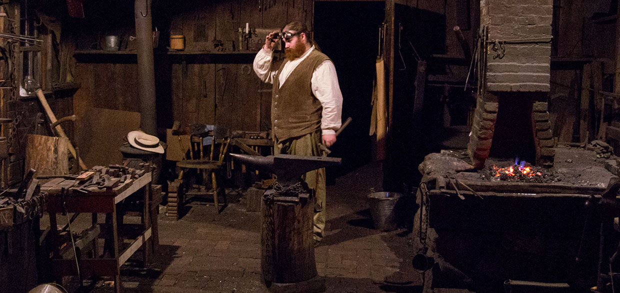 a blacksmith at work in his shop at Black Creek Pioneer Village