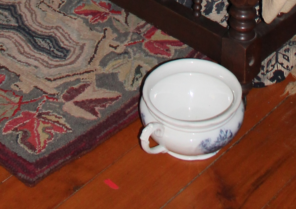 chamber pot sits at the foot of a bed