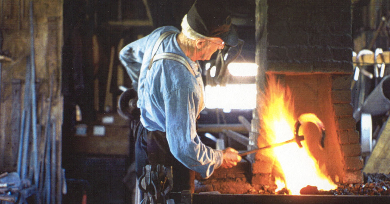 blacksmith uses a forge to fashion horseshoe