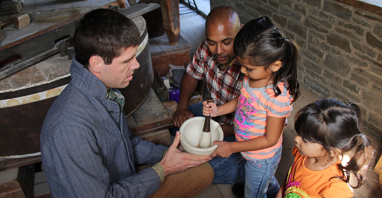 a Black Creek interpreter shows a young visitor how to grind grain in a mortar