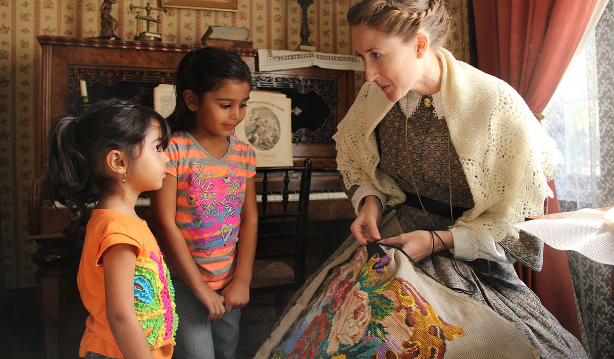 a Black Creek interpreter demonstrates needlepoint for two young visitors