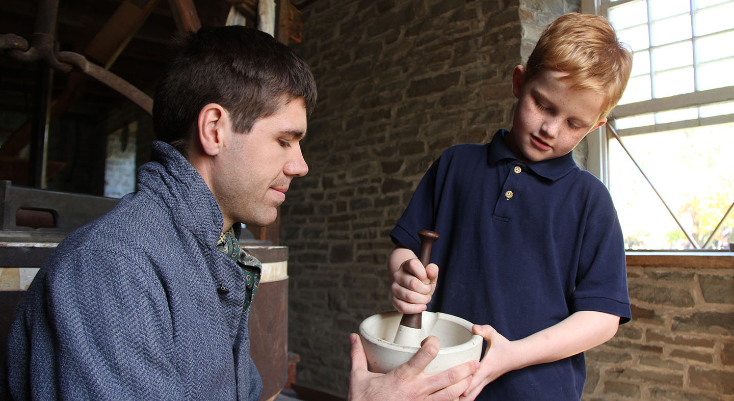 a young visitor to Black Creek practices crushing grain with a pestle