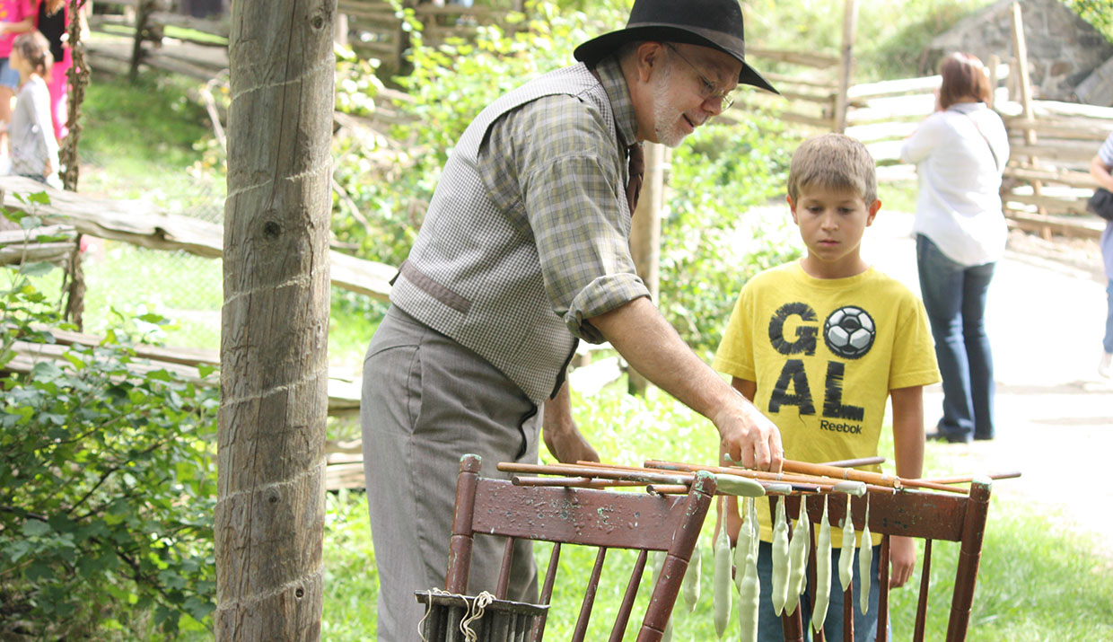 an interpreter at Black Creek Pioneer Village demonstrates how to make candles using tallow