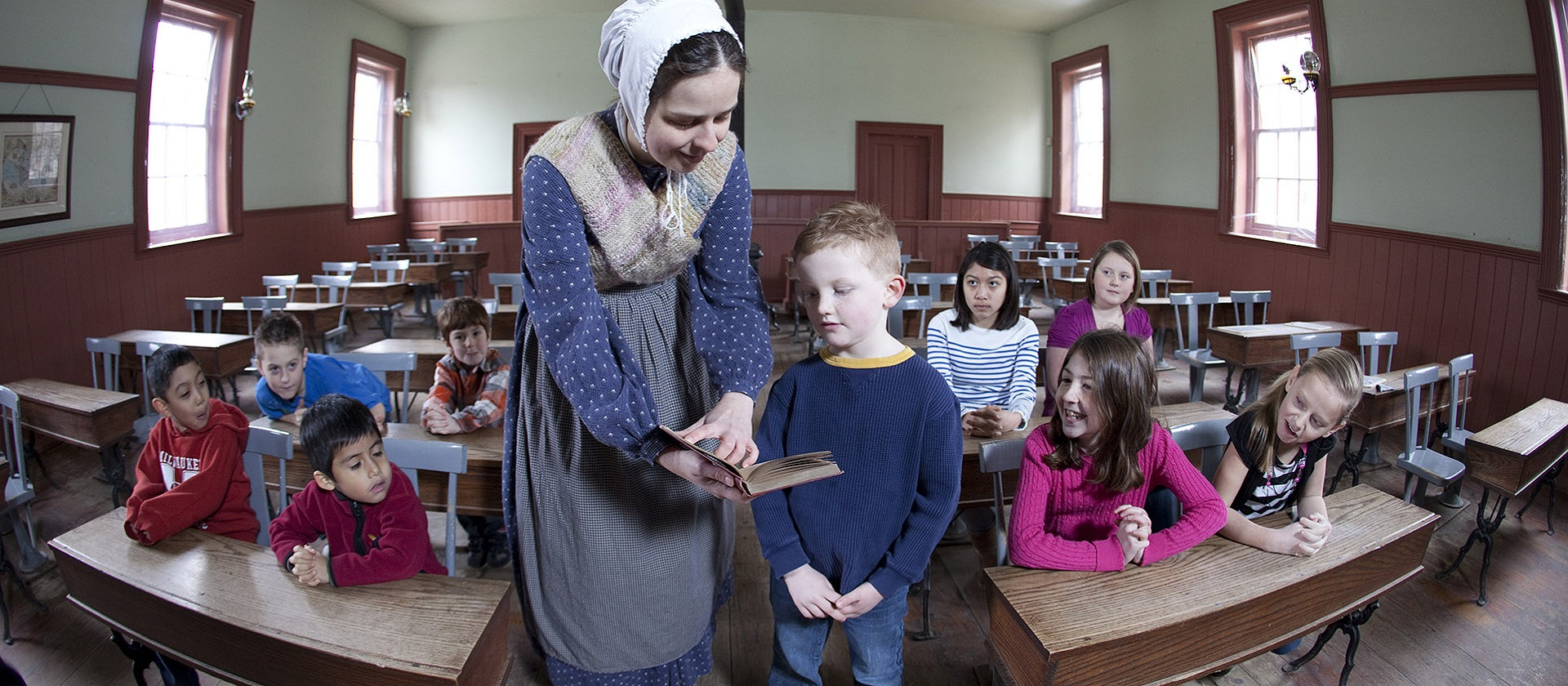 students and teacher in 1860s one room schoolhouse