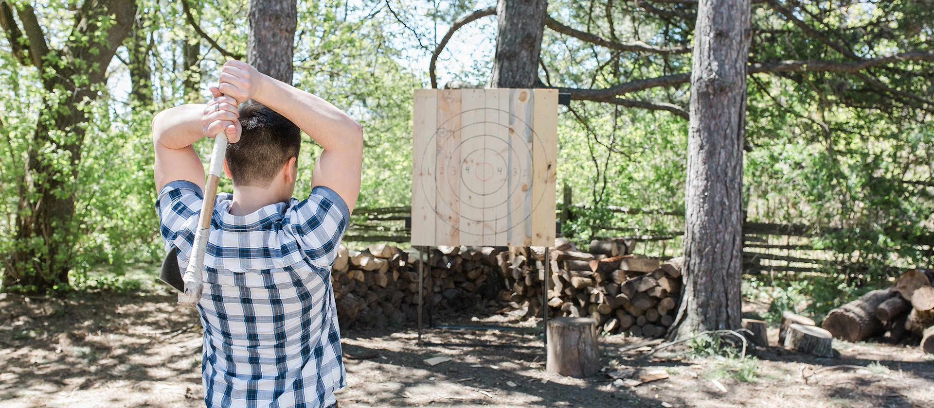 a young man prepares to throw an axe at a target