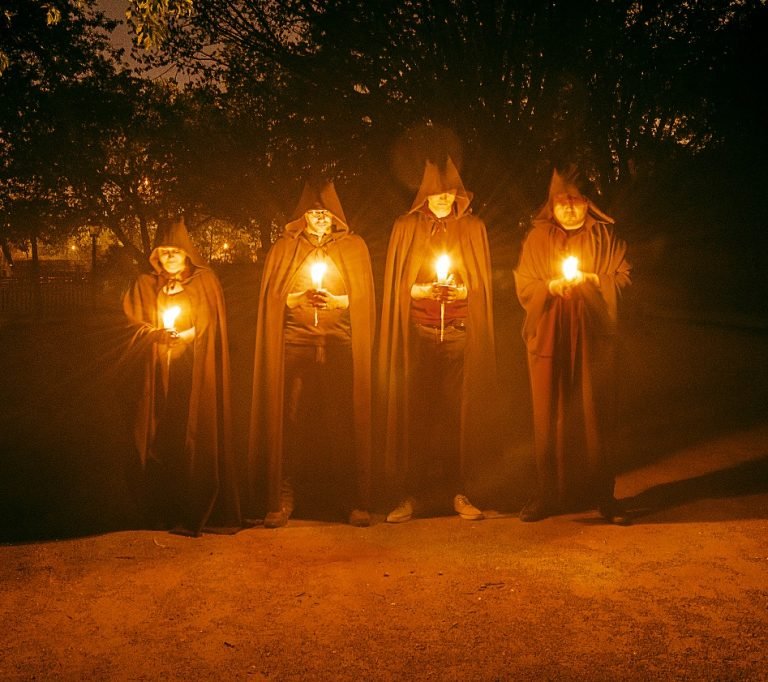 hooded figures hold candles at night