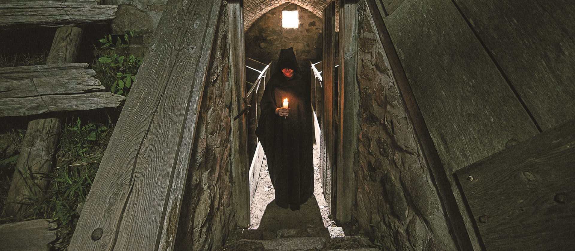 hooded figure with a candle stands at the entrance to the Black Creek apple cellar
