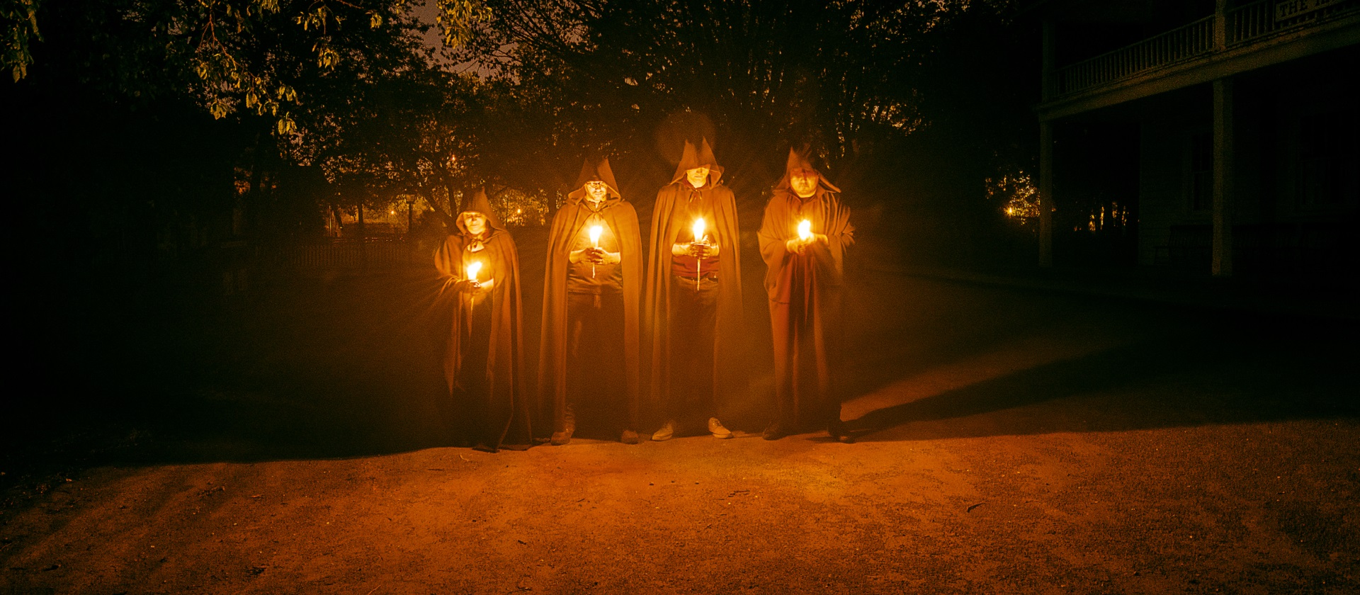 robed figures hold candles on a darkened street at Black Creek Pioneer Village