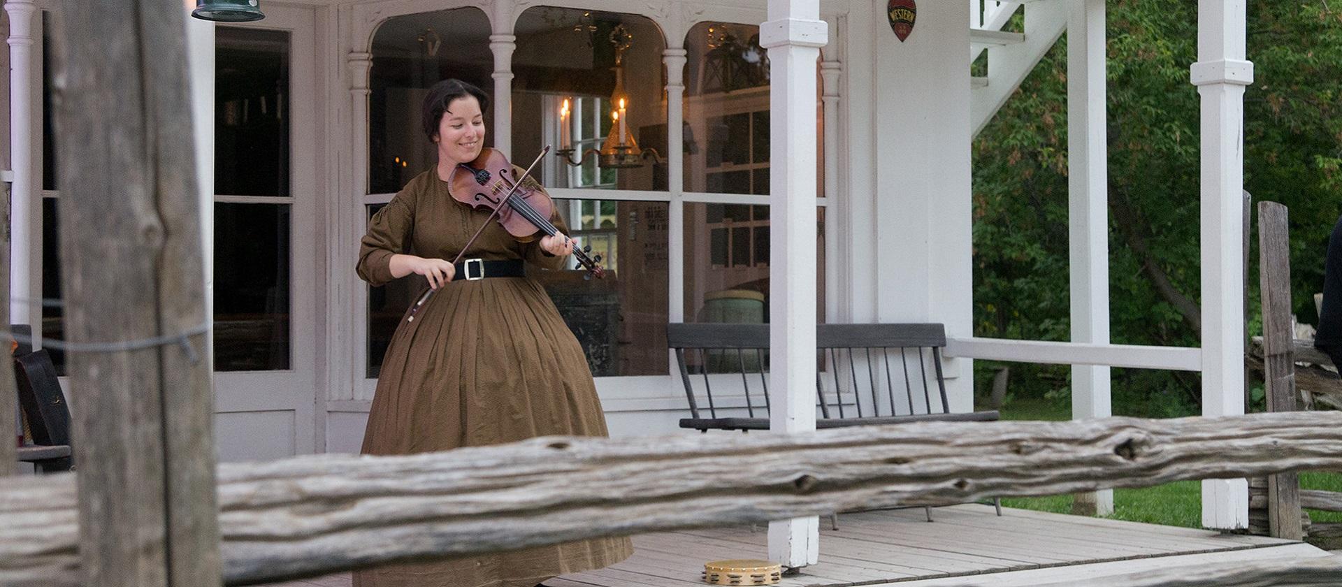 woman in period costume plays a violin at Black Creek Pioneer Village