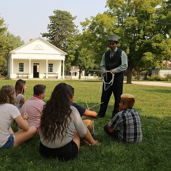costume interpreter speaks to students at Black Creek Pioneer Village