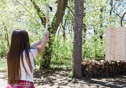 woman throws axe at target