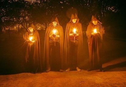 robed figures hold lanterns