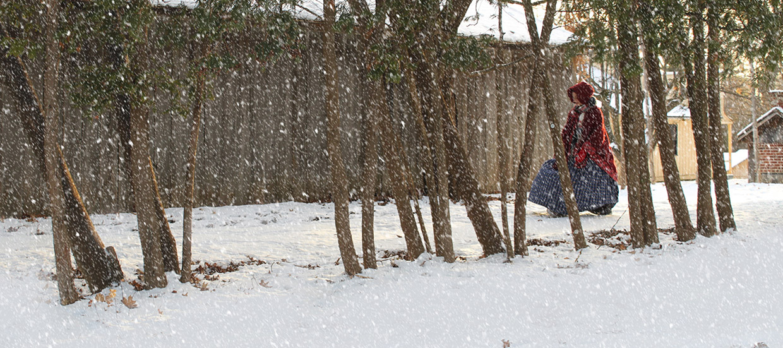 history actor wearing cloak walks through snow at Black Creek Pioneer Village