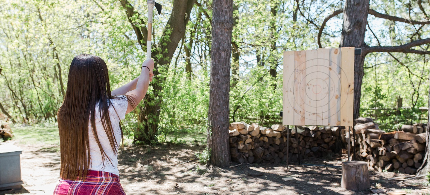 young woman practices axe throwing at Black Creek Pioneer Village