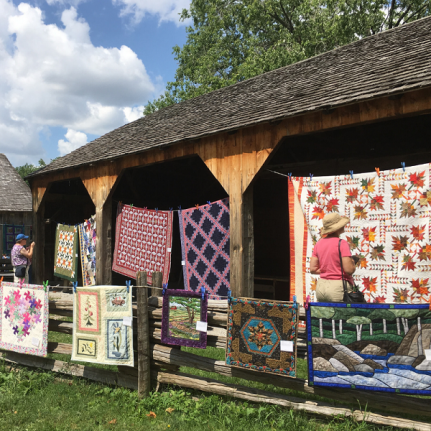 Quilts on display along the fence line at the Village